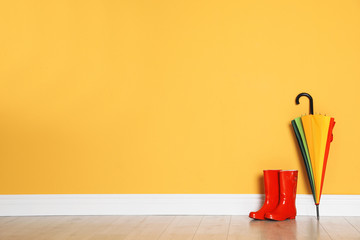 Wall Mural - Beautiful umbrella and gumboots on floor near color wall with space for design