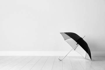 Beautiful open umbrella on floor near white wall with space for design