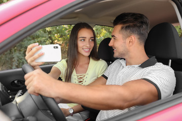 Happy young couple taking selfie in car on road trip