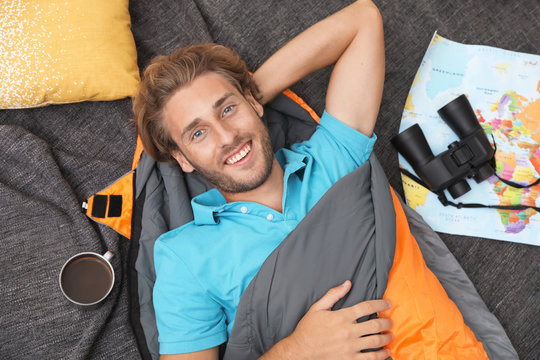 Young man in comfortable sleeping bag on blanket, top view