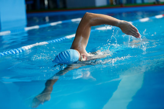Image of sports man in blue cap swimming in pool