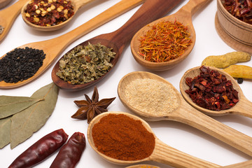 Spice. Spice in a wooden spoon. Herbs. Curry, saffron, turmeric, pepper and other isolated on white background.
