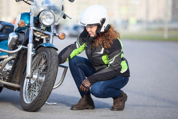 Woman biker trying to repair flat tire on motorcycle at city asphalt road