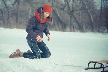 girl is riding a sled on the snow.