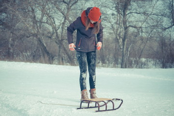 girl is riding a sled on the snow. girl have fun in the winter. Snow Mountain, Girl and Sledge. The girl spends time cheerfully in the winter