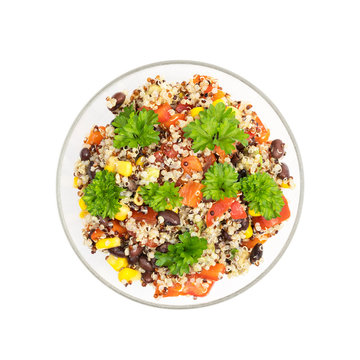 Glass bowl with quinoa salad with red pepper, corn, tomato and black beans, topped with parsley seen directly from above and isolated on white background