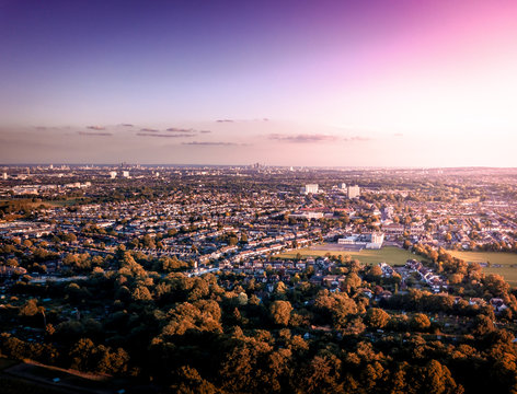 Sunrise aerial view of London City Skyline and famous skyscrapers in the the background above a London housing estate. Taken near the M25, fields and community housing can be seen in the foreground