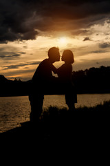 silhouette of romantic lovers with river in thailand with sunset