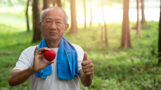 Male senior holding red heart and Happy smile. Health care, Healthy with exercise and Healthy good start, insurance, world heart day