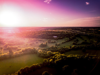 Aerial view of the countryside around London taken at sun set. Dramatic lighting cast on threes and hedgerows as the sun sets, taken from the air