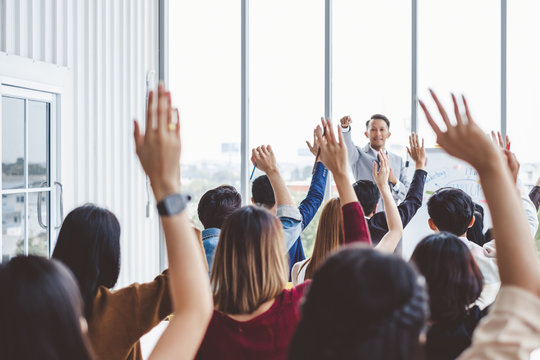 Group of business people raise hands up to agree with speaker in the meeting room seminar