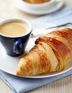 Croissant and a cup of coffee on a plate. Concept for a tasty breakfast. Close up.