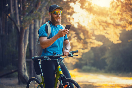bearded man cyclist rides in the forest on a mountain bike.