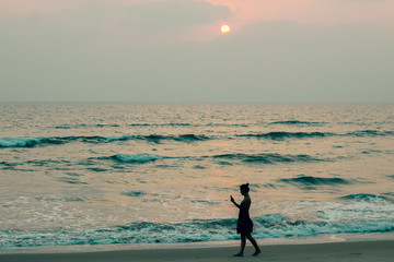 Silhouette of a girl walking along on the beach at sunset