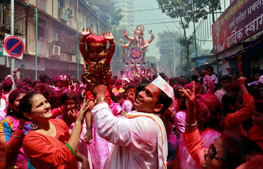 Devotees hold a baby aloft as others carry an idol of Hindu god Ganesh during a procession on the last day of the Ganesh Chaturthi festival, before immersing the idol into the Arabian sea, in Mumbai