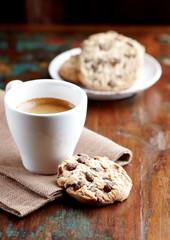 Cup of coffee and chocolate chip cookies. Symbolic image. Concept for a tasty snack. Sweet dessert. Rustic wooden background. Selective focus. Close up.
