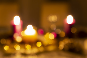 Christmas decoration details on a dining table. Burning candles, christmas balls, stars and gold tinsel. Intentional blurred effect with beautiful bokeh.