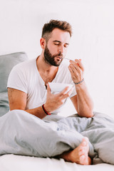 Young man eating breakfast in bed