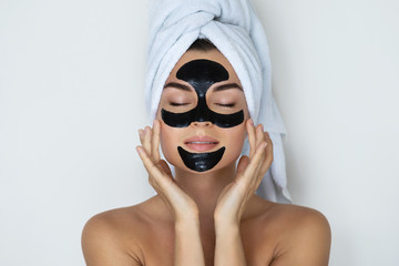 Young and beautiful woman with black peel-off mask on her face