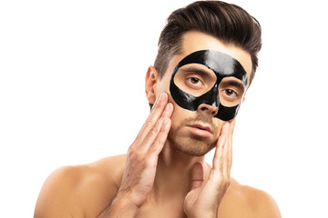 Young guy with a black charcoal mask on his face on white background.
