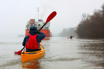 Man in the yellow kayak rowing near a big ship on the Danube River in a cold, cloudy winter day. Winter kayaking.