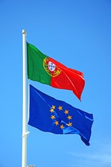 Portuguese and European Union Flags flapping against a blue sky, Algarve, Portugal.