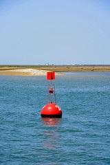 Red channel marker buoy at the edge of the marina with sandbanks to the rear, Olhau, Algarve, Portugal.