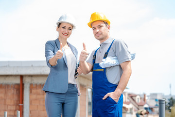Architect and Construction worker on site giving thumbs-up to the camera