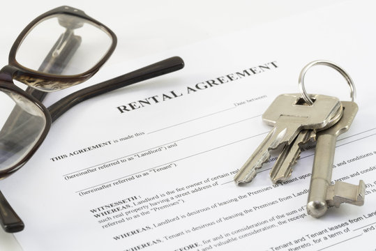 rental agreement document with a set of house keys and glasses
