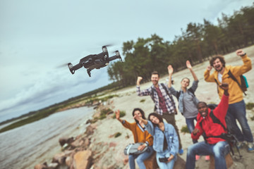 Friendly team spending time together and recording video on the dron for memory about good travel