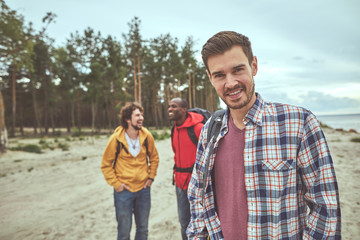 Rejoicing with friends. Waist up portrait of happy man standing and smiling while two of his friends joking on background
