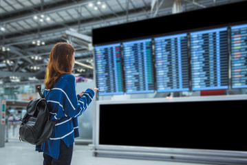 Young woman traveler in international airport looking at the flight information board, checking her flight.