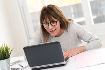 Happy mature woman having a good surprise on laptop