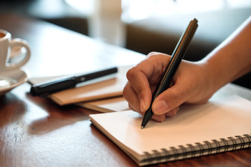 Closeup image of a hand writing down on a white blank notebook with coffee cup on wooden table