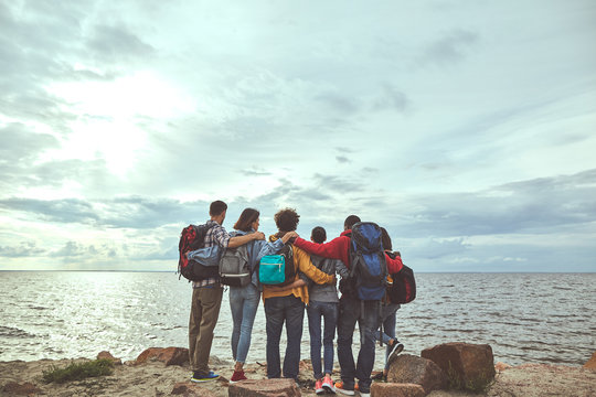 Friendly hugs. Full length portrait of group of people from back making hug and looking at sea