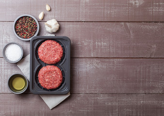 Plastic tray with raw minced homemade beef burgers with spices and herbs. Top view and space for text on top of wooden kitchen table background with tomatoes salt and pepper.