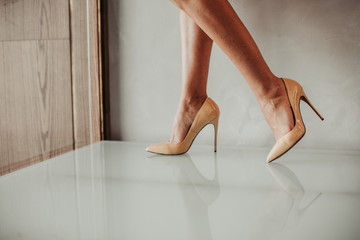 Close up fashion feet wearing fashion beige shoes on high heels inside. Style concept Fototapete