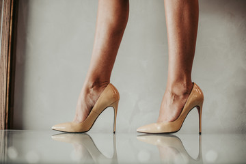 Close up fashion feet wearing contemporary beige shoes on high heels indoor. Vogue concept Fototapete