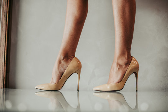 Close up fashion feet wearing contemporary beige shoes on high heels indoor. Vogue concept