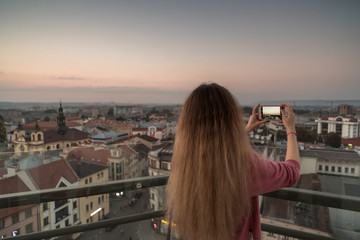 Women taking pictures of the city view at sunset