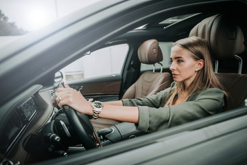 Side view focused woman holding steering wheel while sitting in cozy salon of automobile. Undistracted girl going at work concept