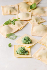 Homemade raw uncooked italian pasta ravioli staffed by spinach ricotta over white marble background. Close up, space