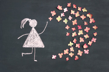 Chalk drawing woman icon with live pink flowers on chalkboard or blackboard. Women's day, feminism, girl power or love concept. Good for postcard