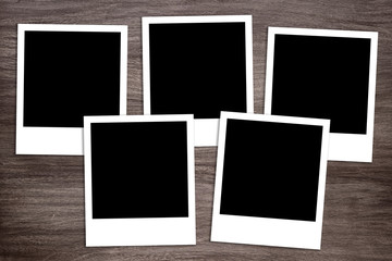 group of five blank instant photo print templates on wooden background