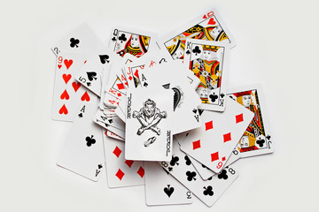 Royal flush playing cards with joker, randomly displaced. Isolated on white background.