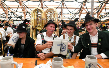Participants from the Oktoberfest parade cheer with beer in a tent during Oktoberfest in Munich