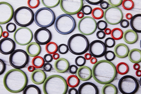 Black, red and gre hydraulic and pneumatic o ring seals of different sizes scattered a white background. Rubber rings. Sealing gaskets for hydraulic joints. Rubber sealing rings for plumbing. Top view