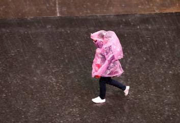 A woman wears a temporary rain coat as she walks during the rain in Bangkok