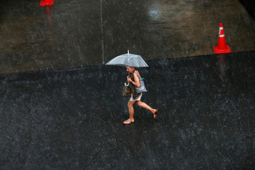 A woman walks under an umbrella during the rain in Bangkok