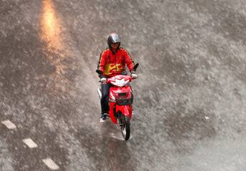 A man drives his motor bike during the rain in Bangkok